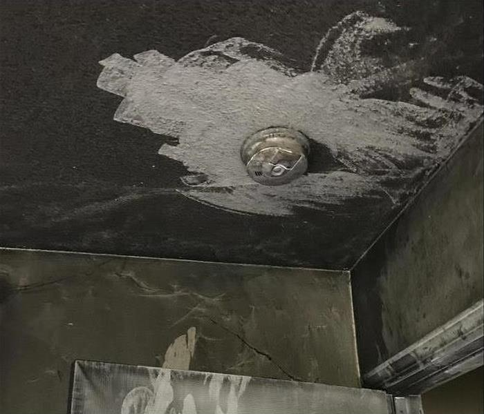 soot damage on the ceiling around a smoke alarm
