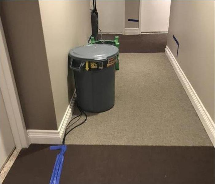 condo hallway with trash can