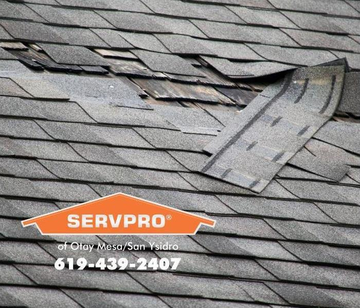 Shingles are shown torn off of a composite shingle roof, revealing hidden water damage below.
